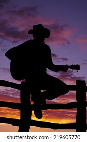 A silhouette of a cowboy sitting on a fence playing his guitar.