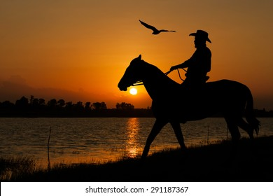 silhouette of Cowboy sitting on his horse at river sunset background
