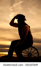 A silhouette of a cowboy sitting on a wagon wheel with his hand on his hat.