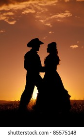 A silhouette of a cowboy and a woman dancing in the sunset.