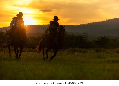 silhouette cowboys riding a horse on the lawn while the sun sets
