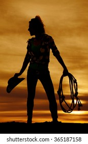 A silhouette of a cowgirl holding on to her hat and rope in the outdoors