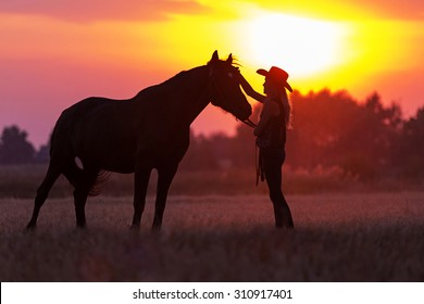 Silhouette of cowgirl and a horse
