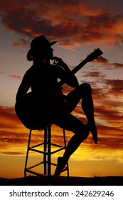 A silhouette of a cowgirl sitting on a stool holding her guitar thinking.