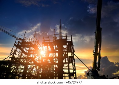 Silhouette crane construction equipment,Industrial construction cranes and building over amazing sunset sky abstract background,dramatic