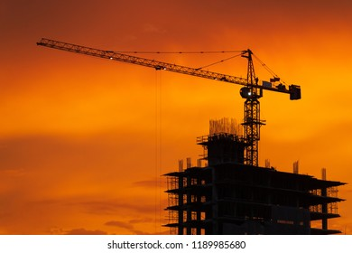 Silhouette crane in construction site at sunset