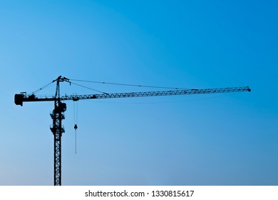 Silhouette of crane on blue sky background.