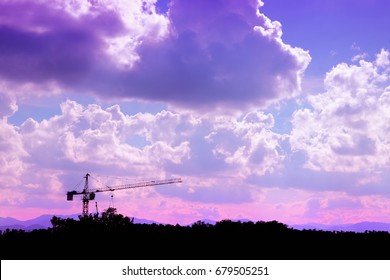 Silhouette crane on construction site with the cloud on sky background. purple tone
