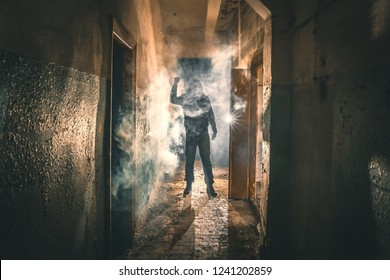 Silhouette of criminal or maniac with knife in hand in old scary corridor, man killer with cold weapon, toned