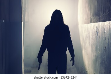 Silhouette of criminal or maniac or rapist with knife in hand and long hair in old scary corridor, man killer with cold weapon, halloween and thriller movie atmosphere, toned