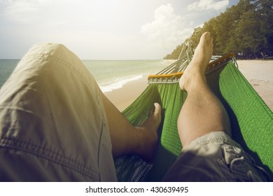 Silhouette of cropped shot Man relaxing in the hammock set on the beach,flare light