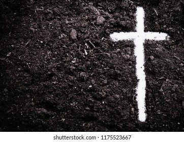 The silhouette of cross against of soil background. The cross as symbol for Jesus Christ. Christianity, religion, faith concept.