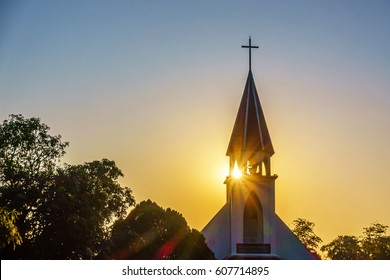 The silhouette of the cross and church bell tower in sunrise