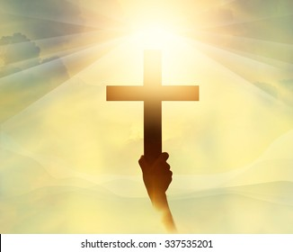Silhouette the cross in hand, religion symbol in light and landscape over a sunrise, background, religious, faith concept