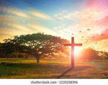 Silhouette cross on meadow sunrise background
