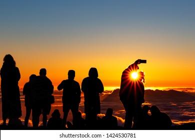 Silhouette of crowd enjoying the sunset atop Mount Haleakala on