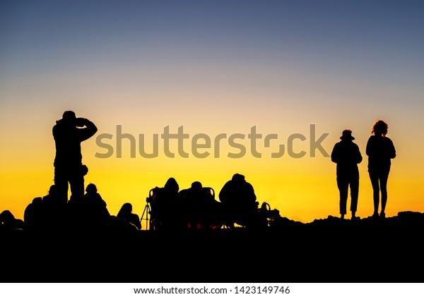 silhouette-crowd-enjoying-sunset-atop-60