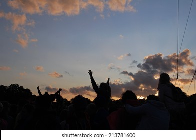 silhouette of crowd at outdoor festival at sunset