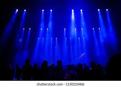 Silhouette of crowd of people at music festival. Blue stage lights