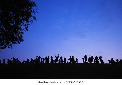 Silhouette crowd people are standing under the tree with blue sky, blank space.