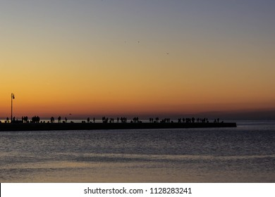 Silhouette of a crowd of people watching the sunset from a dock in Trieste, Italy