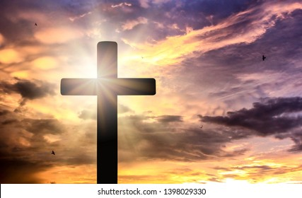 Silhouette of crucifix cross at sunset time with holy and light background.