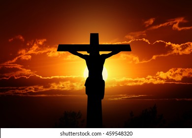 Silhouette crucifixion of Jesus and the sunset.