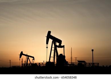 Silhouette of crude oil Bpu pump in oilfield at sunset