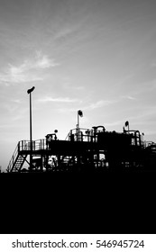 Silhouette of crude oil manifold mini plant in the oilfield at sunset - black and white