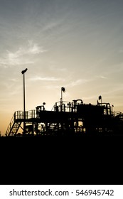 Silhouette of crude oil manifold mini plant in the oilfield at sunset