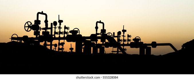 Silhouette of crude oil manifold in the oilfield at sunset