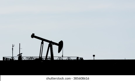Silhouette of crude oil pump at cloudy sunset in oil field.