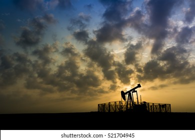 Silhouette of crude oil pump in oilfield at cloudy sunset.