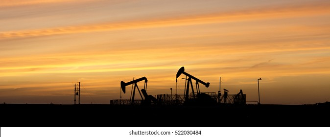 Silhouette of crude oil pump in oilfield at sunset - wide crop - black and white