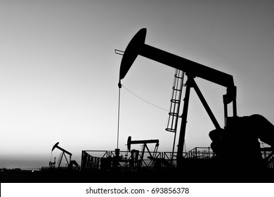 Silhouette of crude oil pump in the oilfield at sunset golden hour - Black and white edit