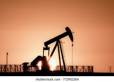 Silhouette of crude oil pump in oilfield at sunset