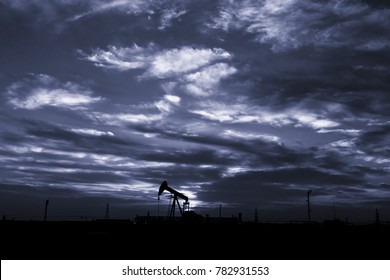 Silhouette of crude oil pump in oilfield at sunset blue hour.