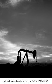 Silhouette of crude oil pump at sunset blue hour in the oilfield -black and white