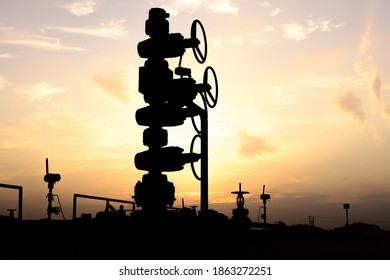 Silhouette of a crude oil well head in the oilfield at sunset