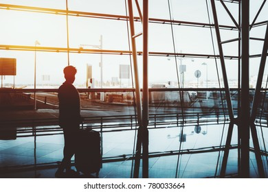 Silhouette of curly black female standing indoors with a huge rolling bag in front of panoramic window and facade of modern airport terminal with strong reflections on the floor and sunny day outside