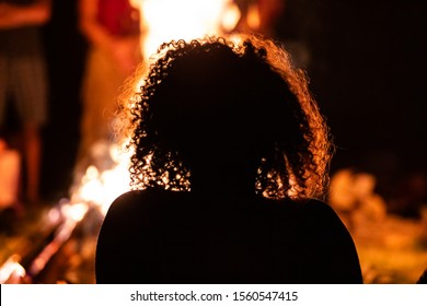 silhouette of a curly hair woman sitting in the front of the fire, seen from behind during dark night campfire, blurred background