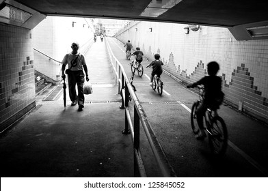 silhouette of cycling kids and father and an old walking man in the end of tunnel with back light in hong kong street