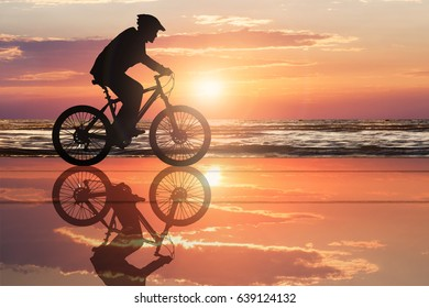 Silhouette Of A Cyclist At Beach With Dramatic Sky During Sunset