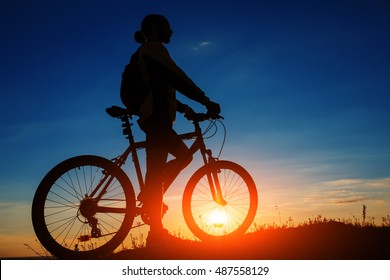 Silhouette of cyclist and a bike on sky background during sunset