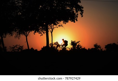 A silhouette of a cyclist with a bright sunset in the background. Enjoying a hot summer evening at the Park at River Walk, Bakersfield, CA.