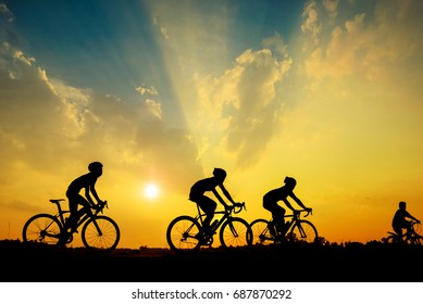 Silhouette of cyclist with friend in motion on the background of beautiful sunset