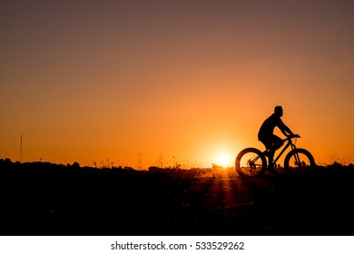 Silhouette of cyclist in motion at beautiful sunset.