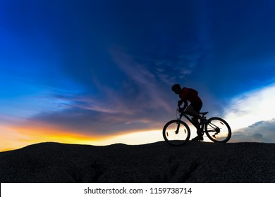 Silhouette of cyclist in motion on the background of beautiful sunset,ride bicycle on sunset background