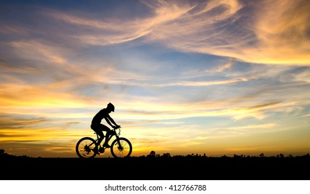 Silhouette of cyclist in motion on the background of beautiful sunset