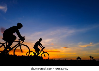Silhouette of cyclist in motion on the  Colorful  sunset background.